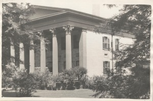 A view of the front of a building built circa 1828 that is now owned by Wesleyan University. Fluted Corninthian columns grace the portico that leads to a massive front door. Leafy trees surround the building.
